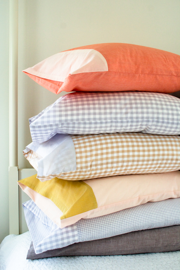 5 pillows with colorful pillowcases stacked on each other