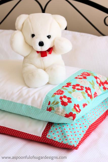 white teddy bear on top of 2 pillows