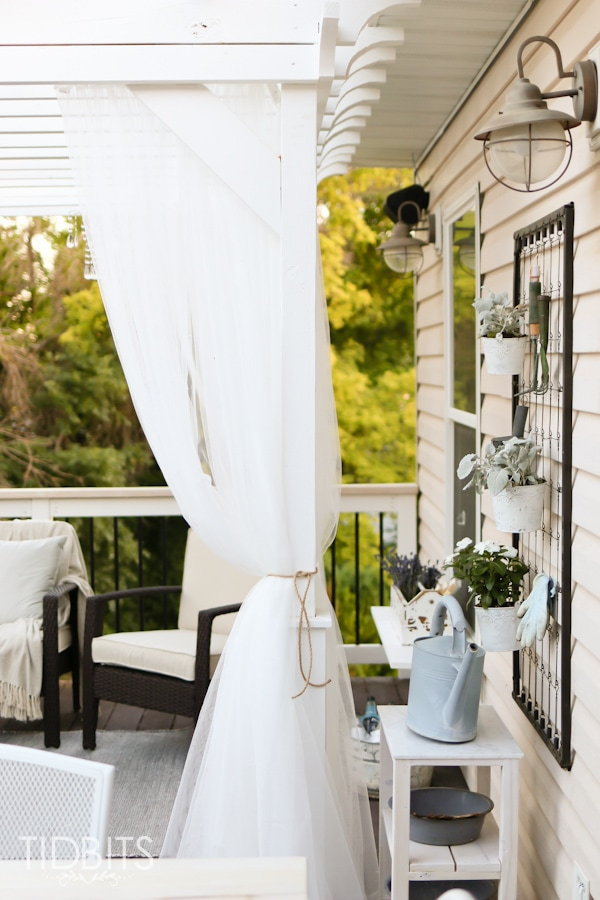 Curtained pergola on a deck for a beautiful and cozy retreat. Deck makeover by TIDBITS.