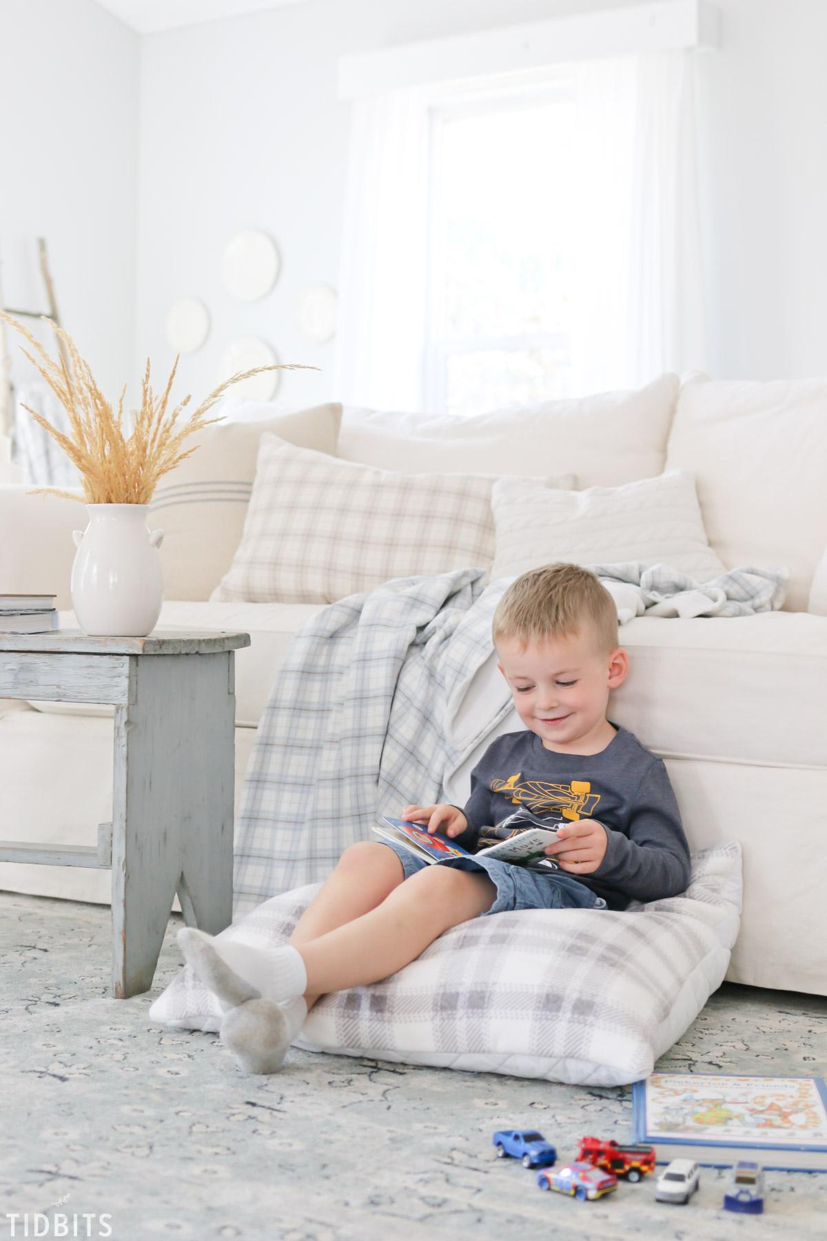 boy reading book on floor cushion
