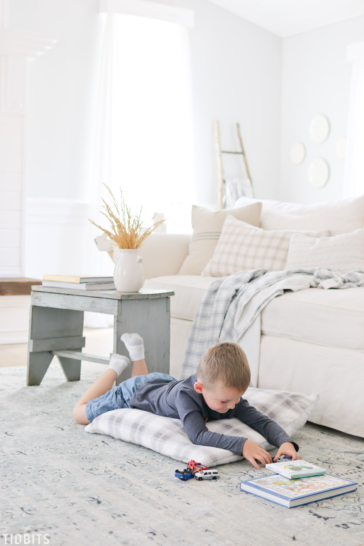 boy laying of quilted floor cushion playing cars