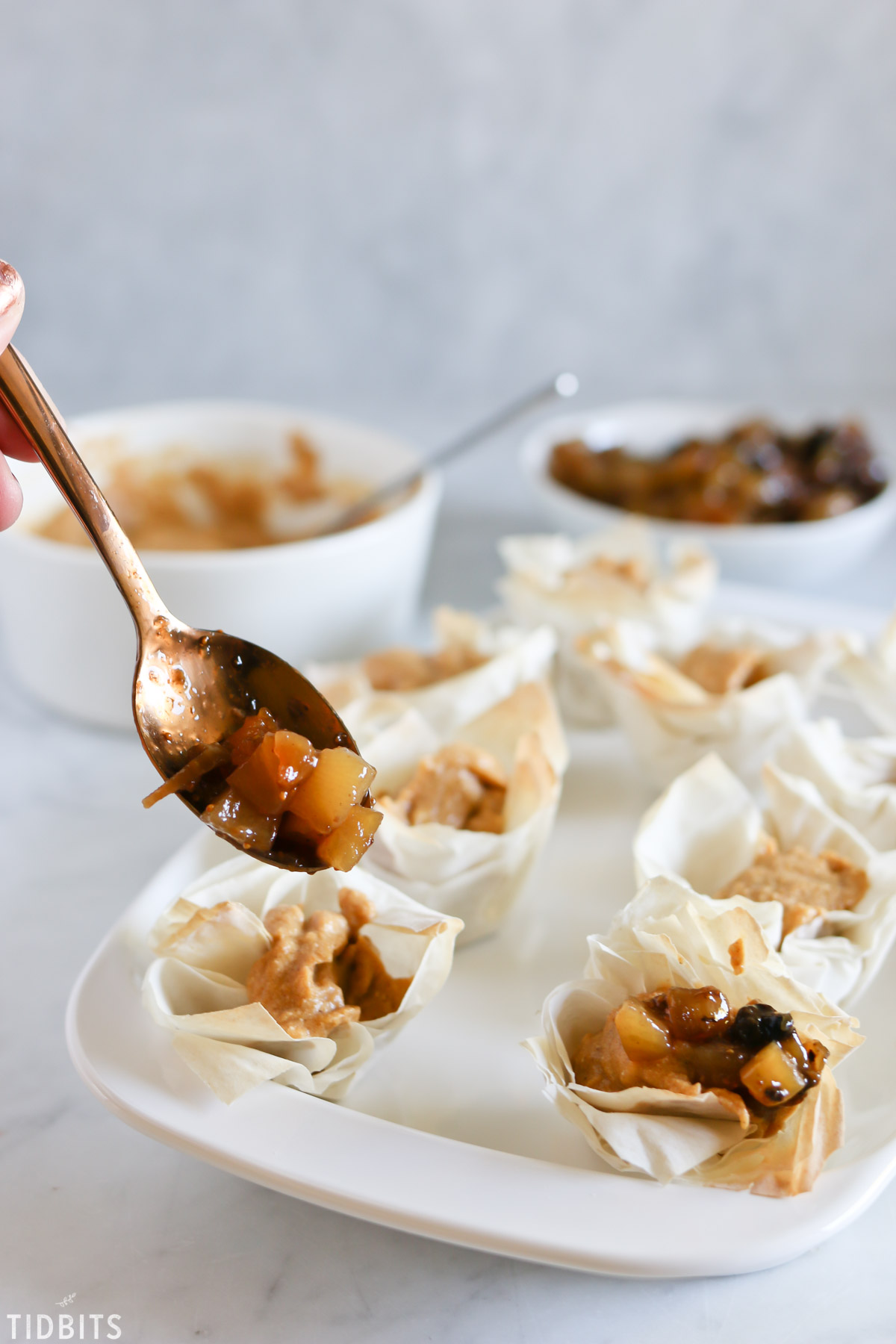 Phyllo cups with pumpkin filling and topped with cooked apples.