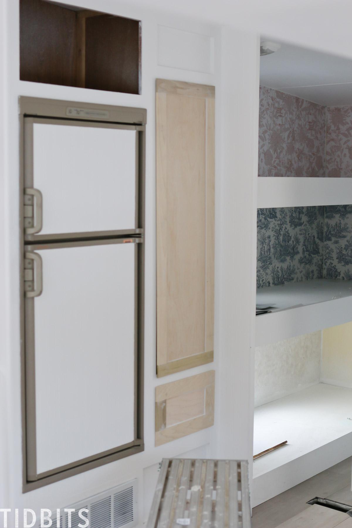 RV kitchen fridge covered in wallpaper