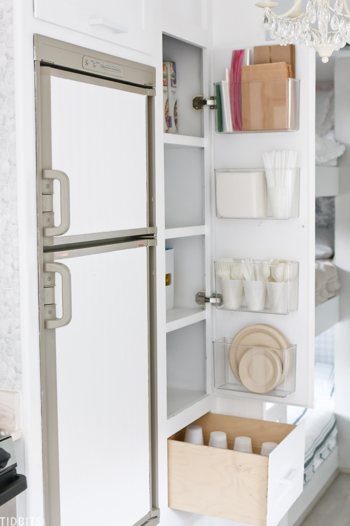 Store paper products on the inside of the kitchen cupboard with vertical storage shelves.