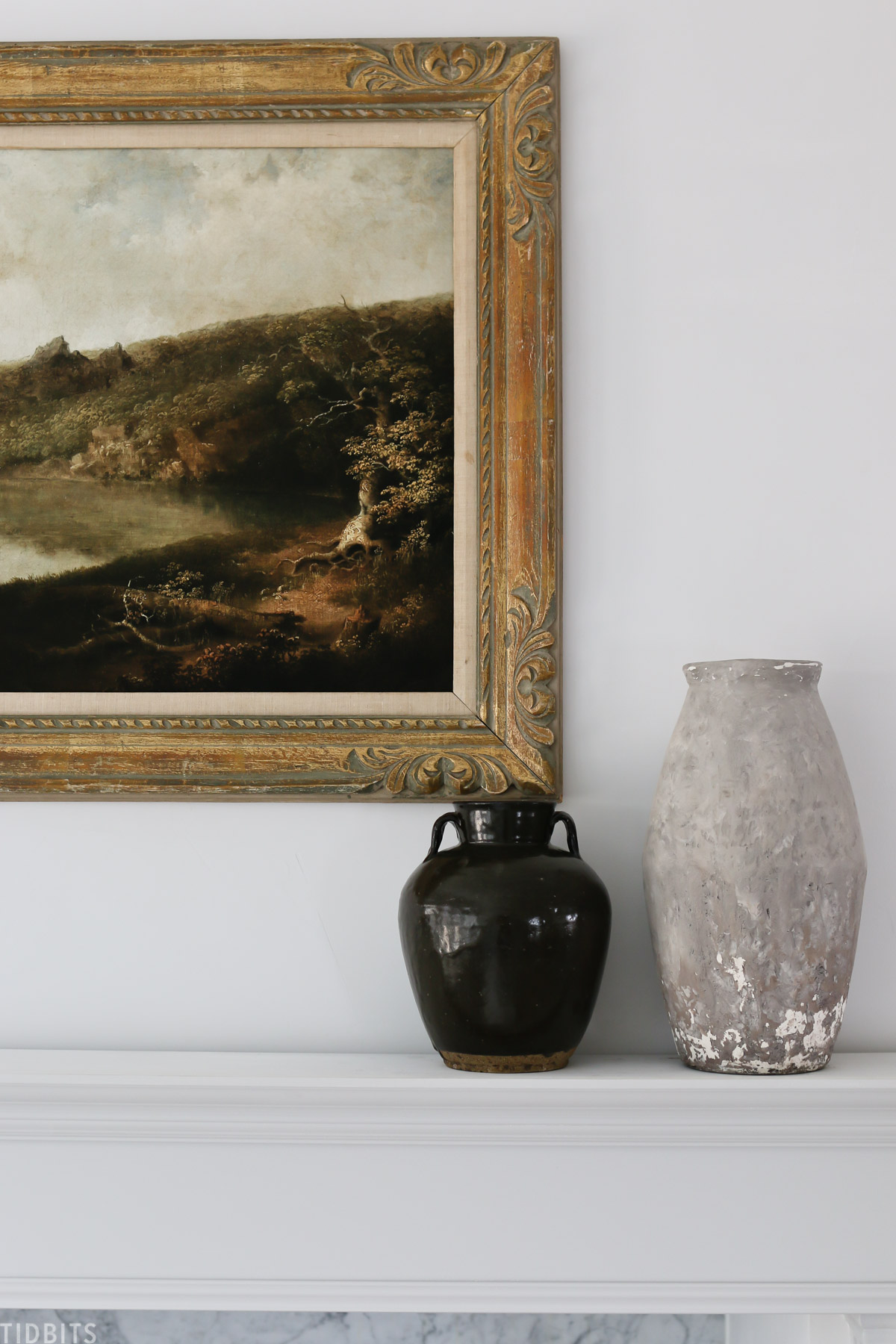 framed vintage wall art hanging above mantel with two antique vases on the mantel