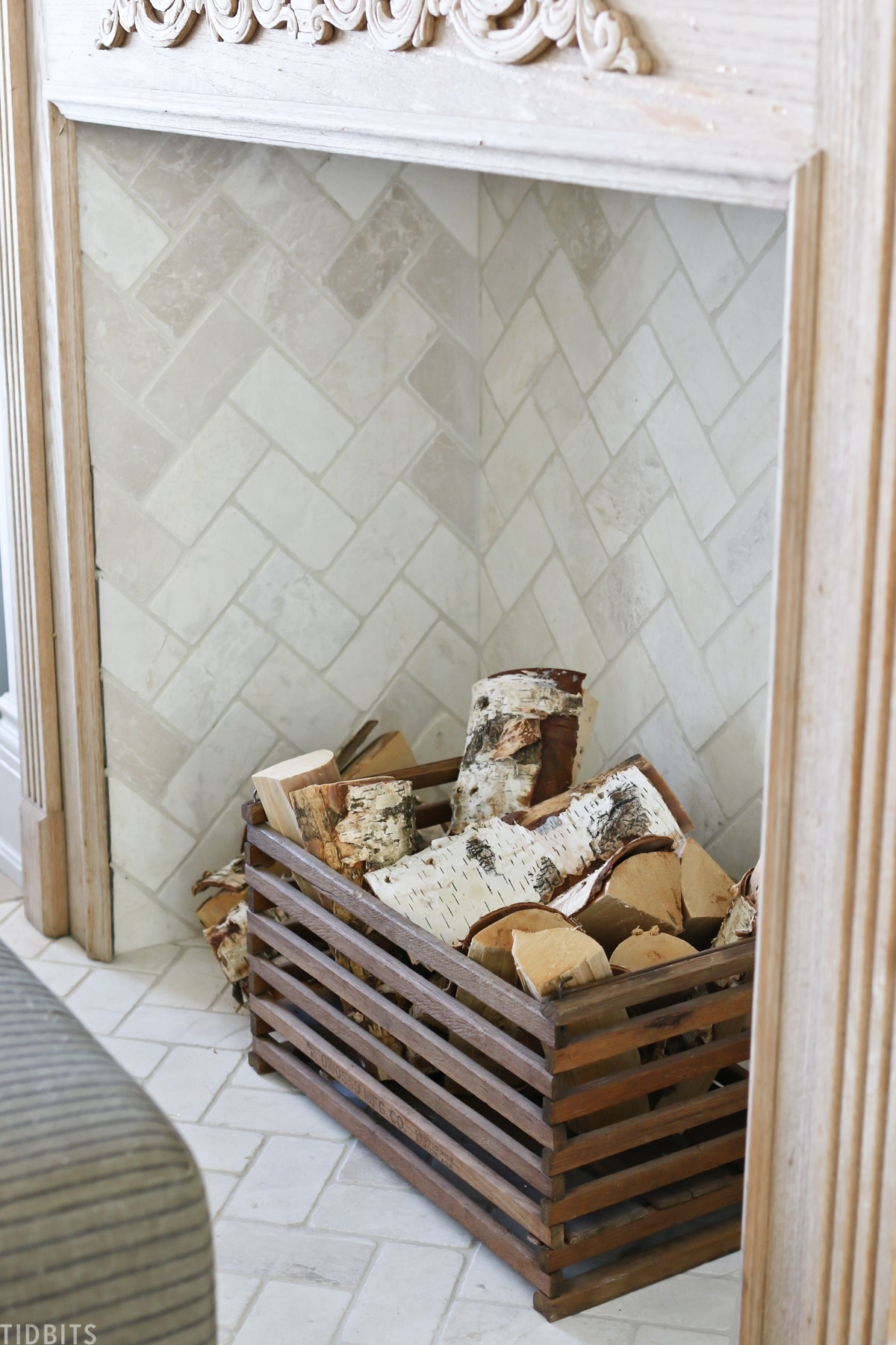 pieces of firewood placed in wooden basket in front of fireplace