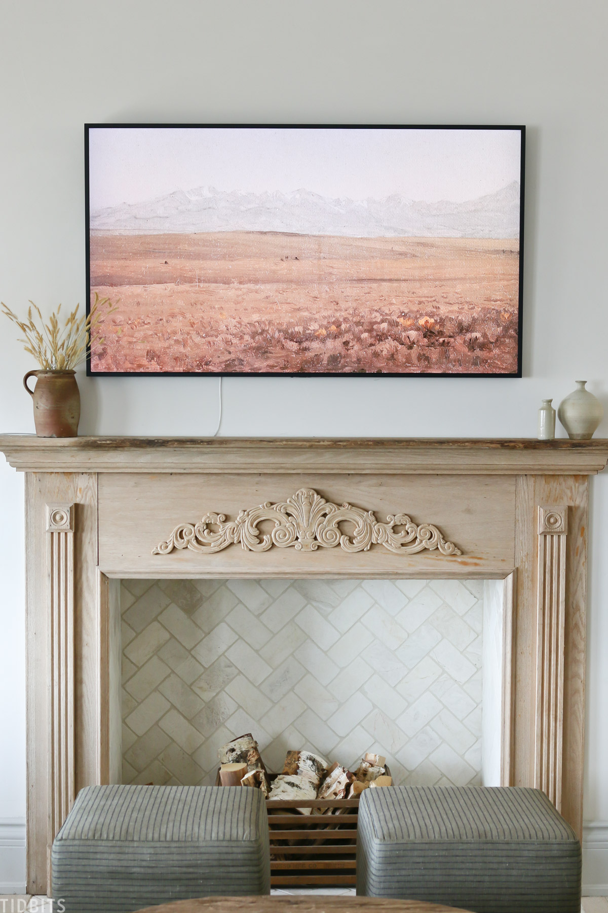 faux fireplace mantel with wood placed inside fireplace and Samsung TV above mantel