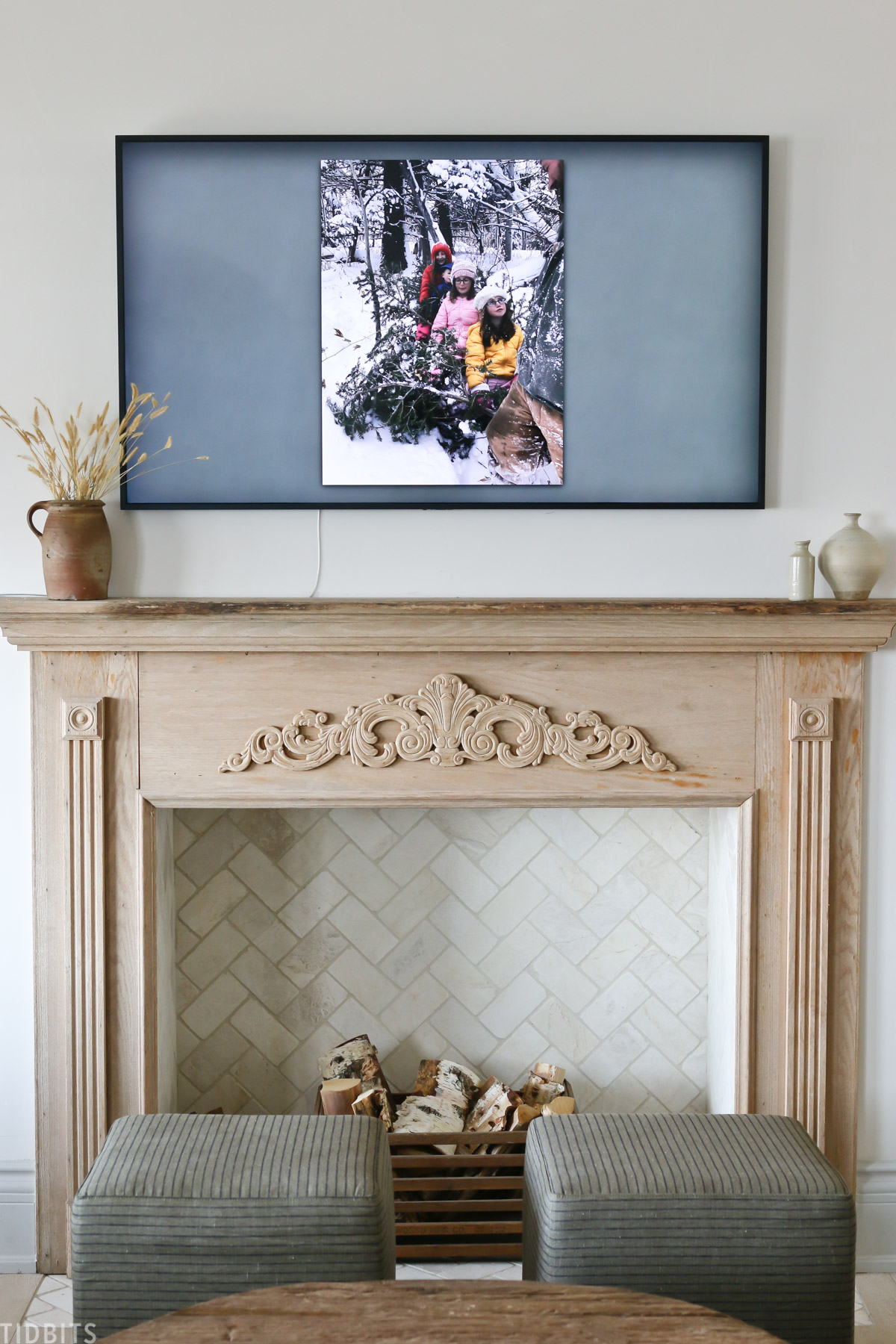 faux fireplace mantel with wood placed inside fireplace and Samsung Frame TV above mantel