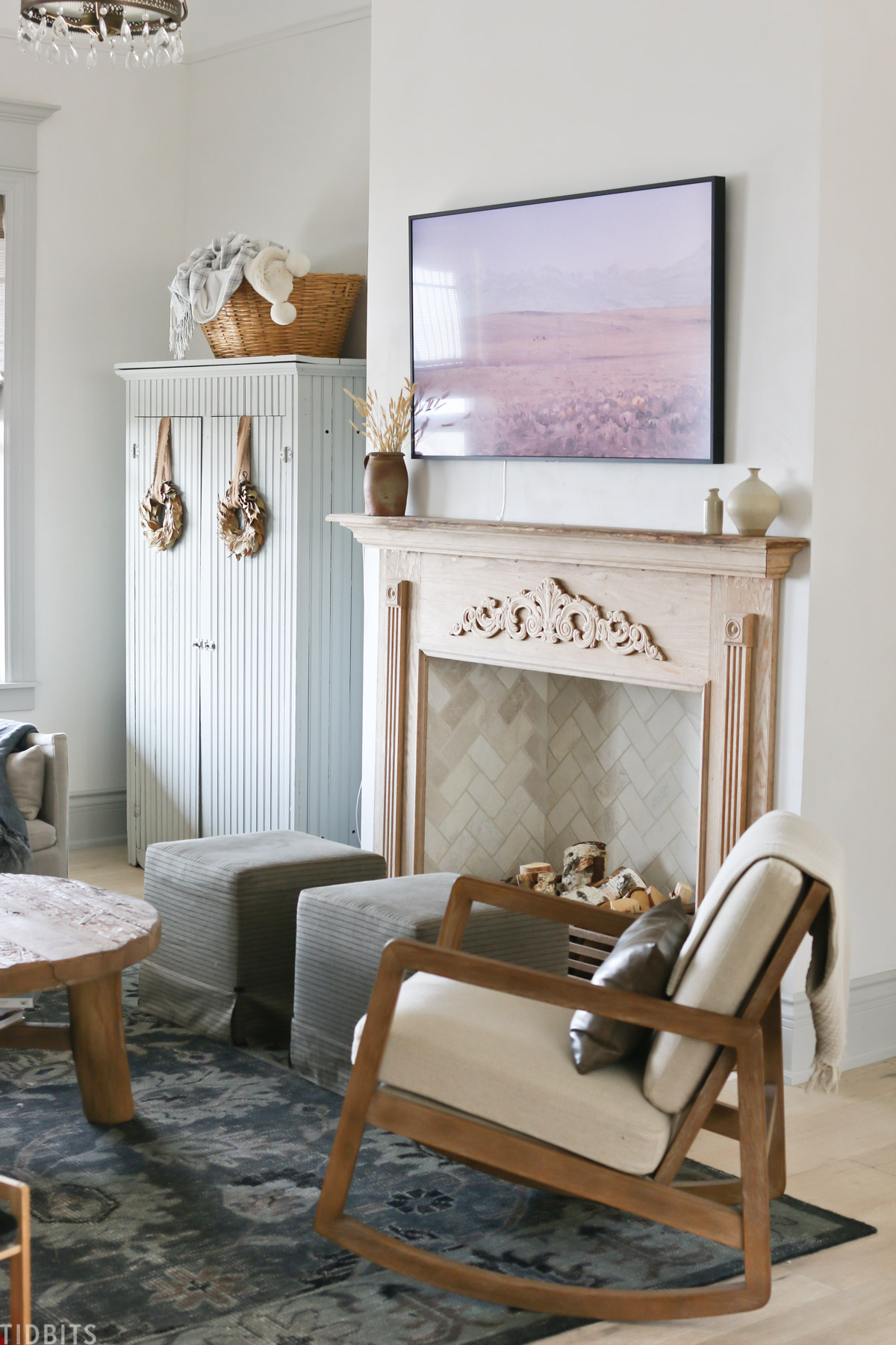 faux fireplace mantel with wood placed inside fireplace and Samsung TV Frame above mantel