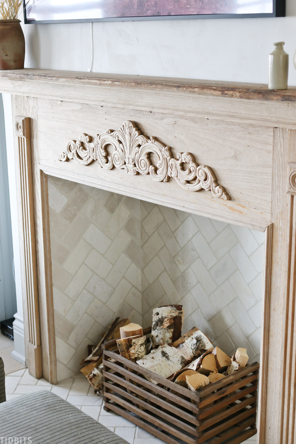 firewood placed in wooden crate within faux fireplace