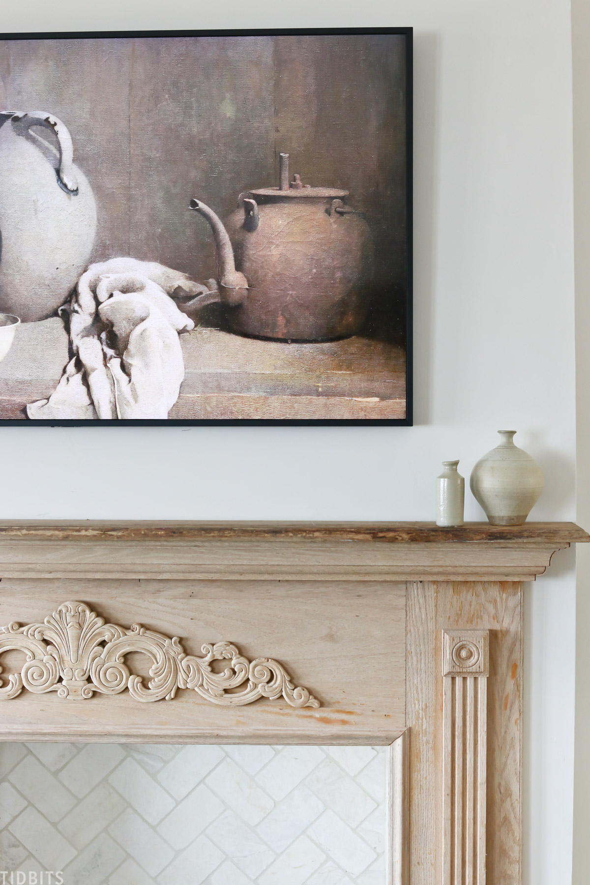 two pieces of pottery placed on faux mantel with antique painting on wall above mantel