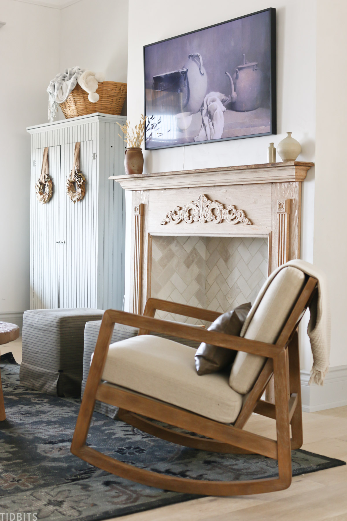 wooden rocking chair in front of faux fireplace with home decor items placed throughout living room