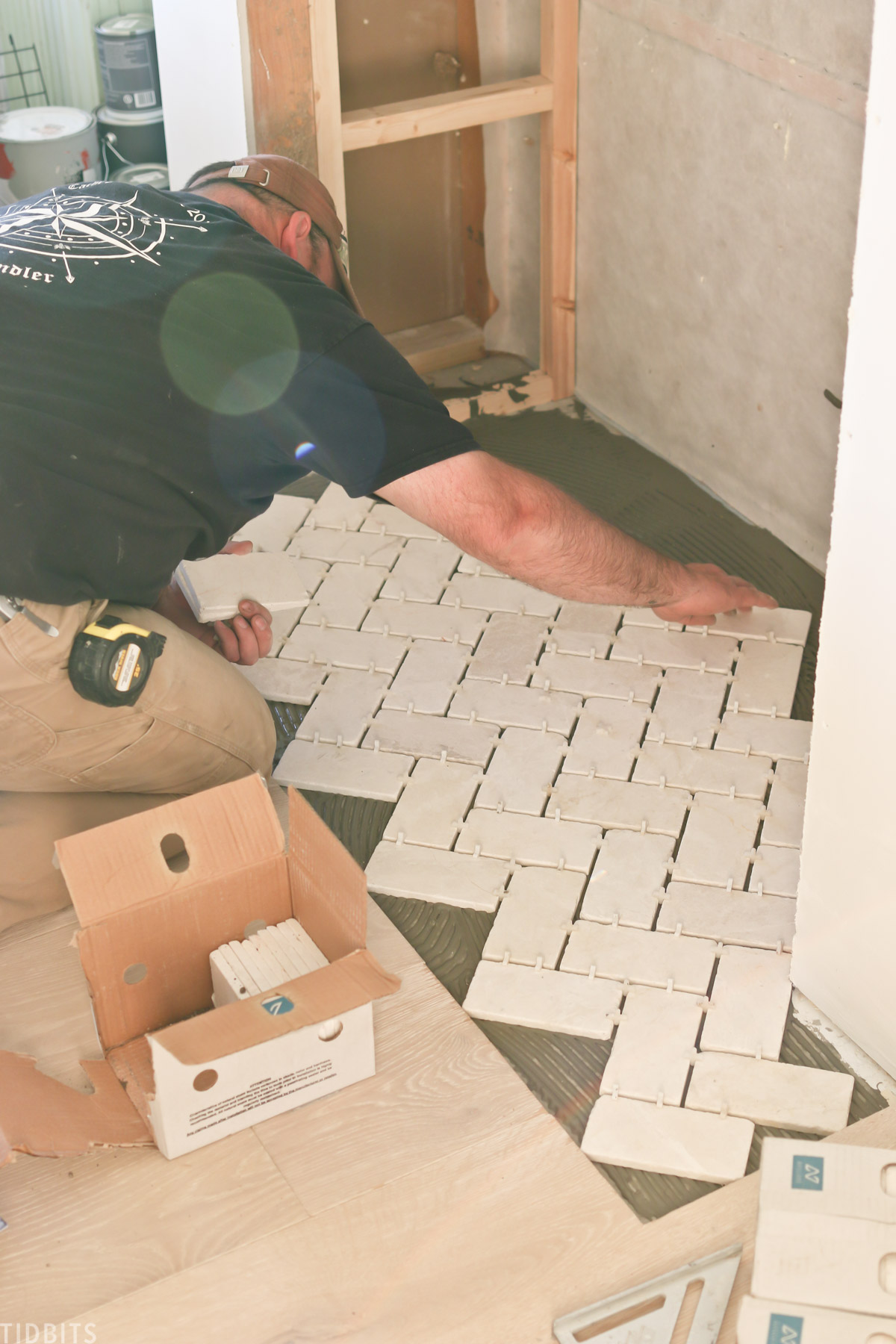 man laying out white tiles on floor