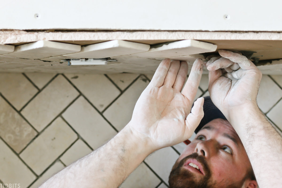 man applying tiles to the top part of a faux fireplace