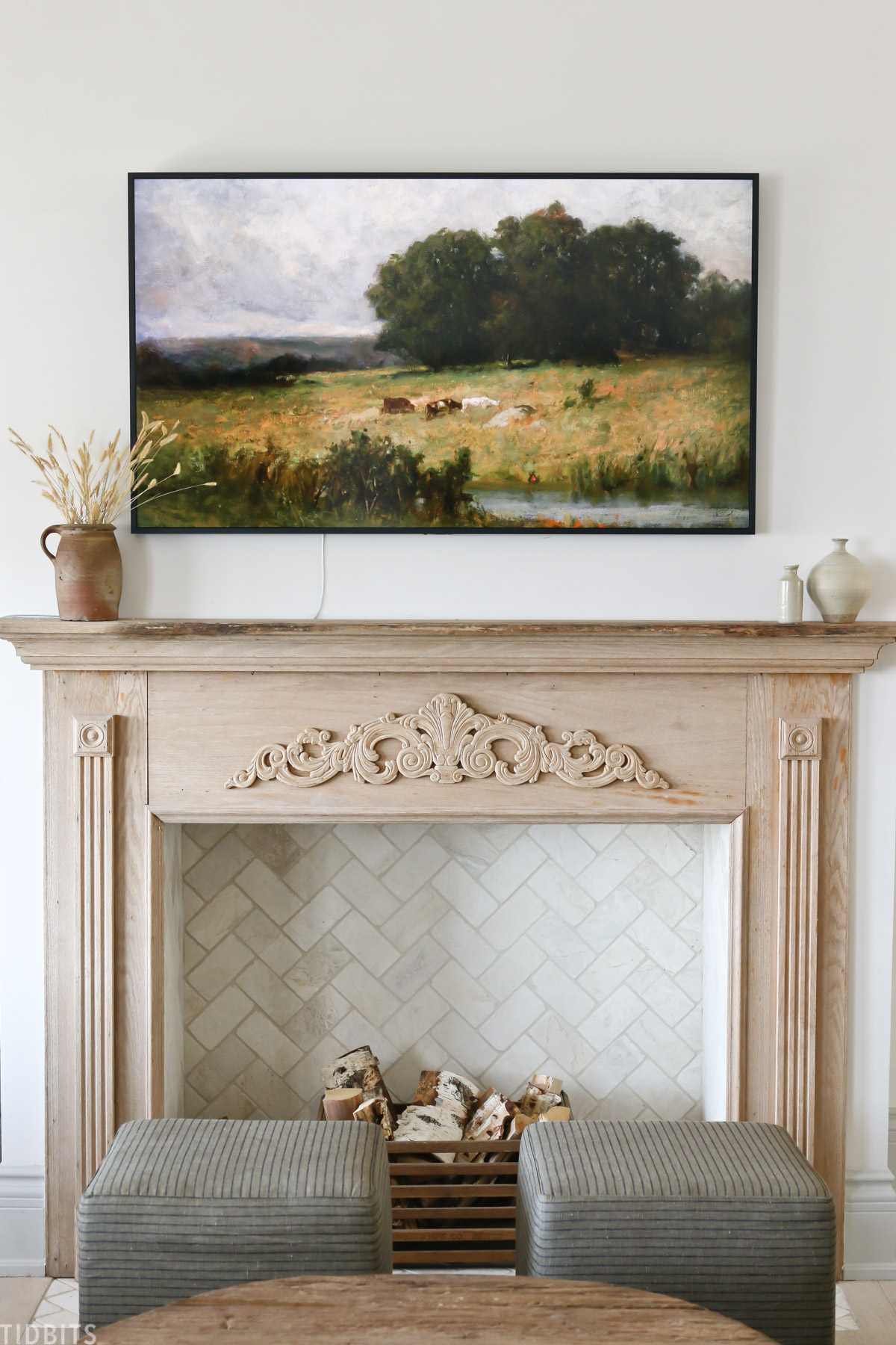 faux fireplace mantel with wood placed inside fireplace and vintage painting above mantel