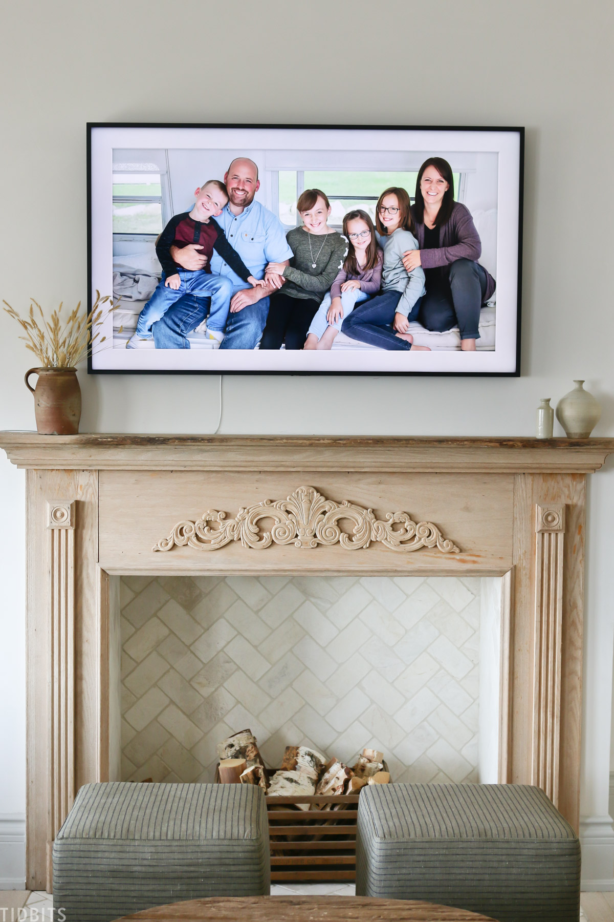faux fireplace mantel with wood placed inside fireplace and family portrait above mantel