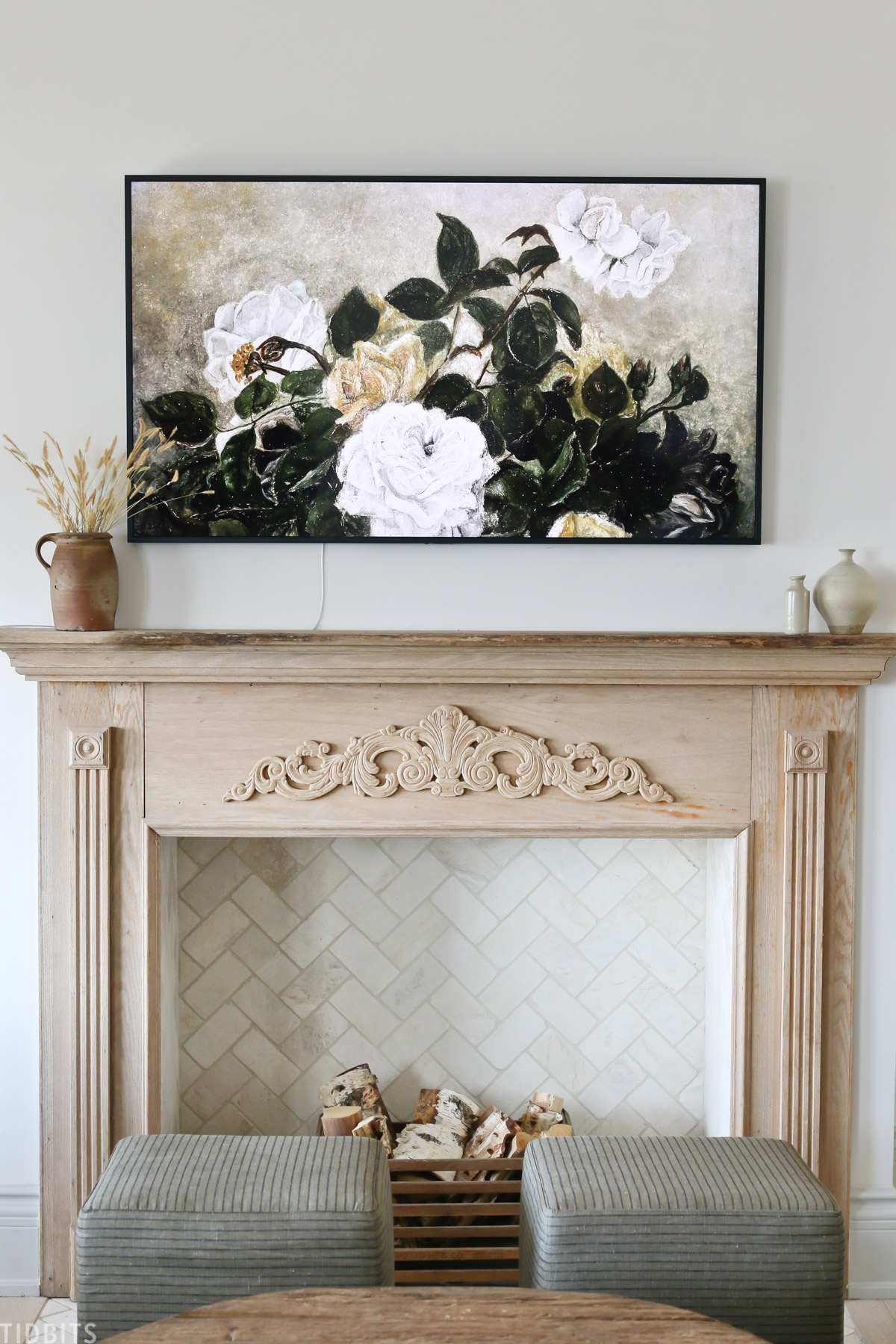 faux fireplace mantel with wood placed inside fireplace and flower painting above mantel
