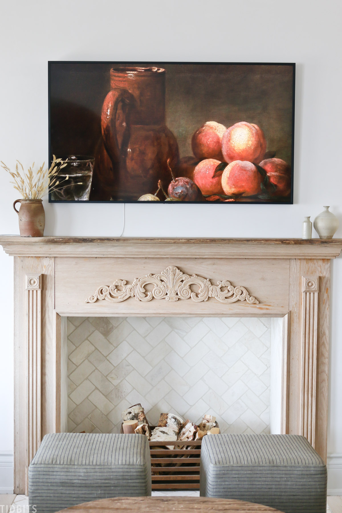 faux fireplace mantel with wood placed inside fireplace and fruit painting above mantel