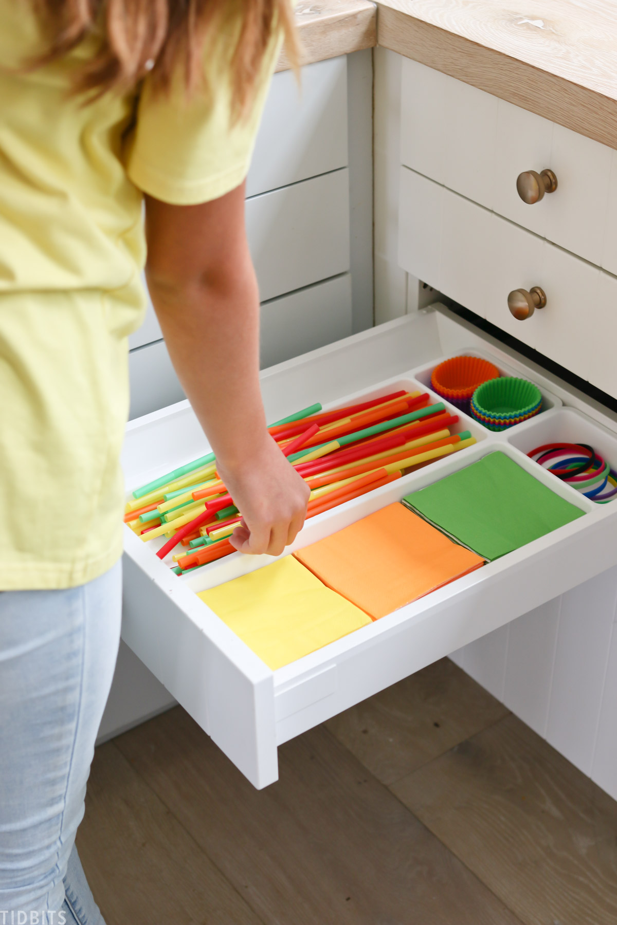 hand is reaching into drawer containing straws, napkins, cupcake liners, and silicone wristbands