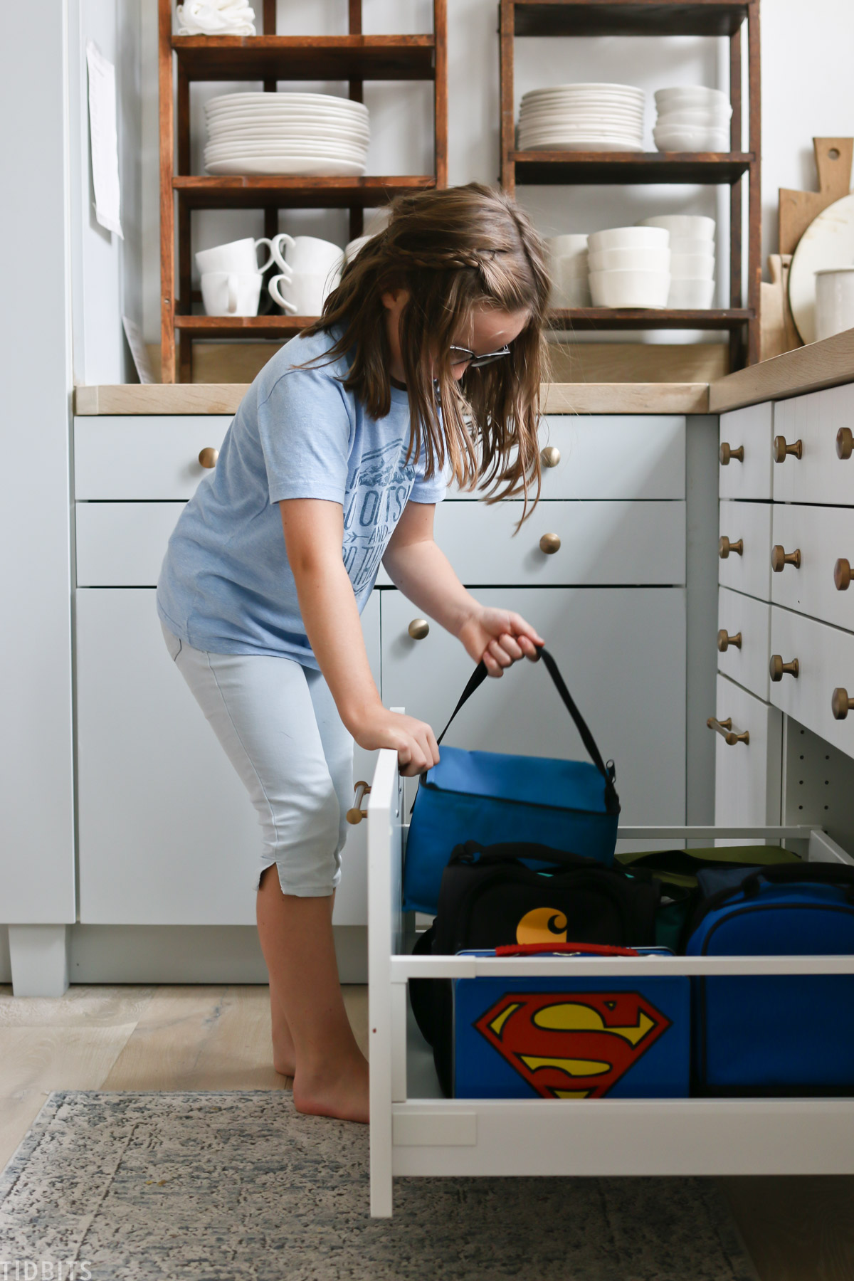 young girl grabs blue lunchbox out of kitchen drawer