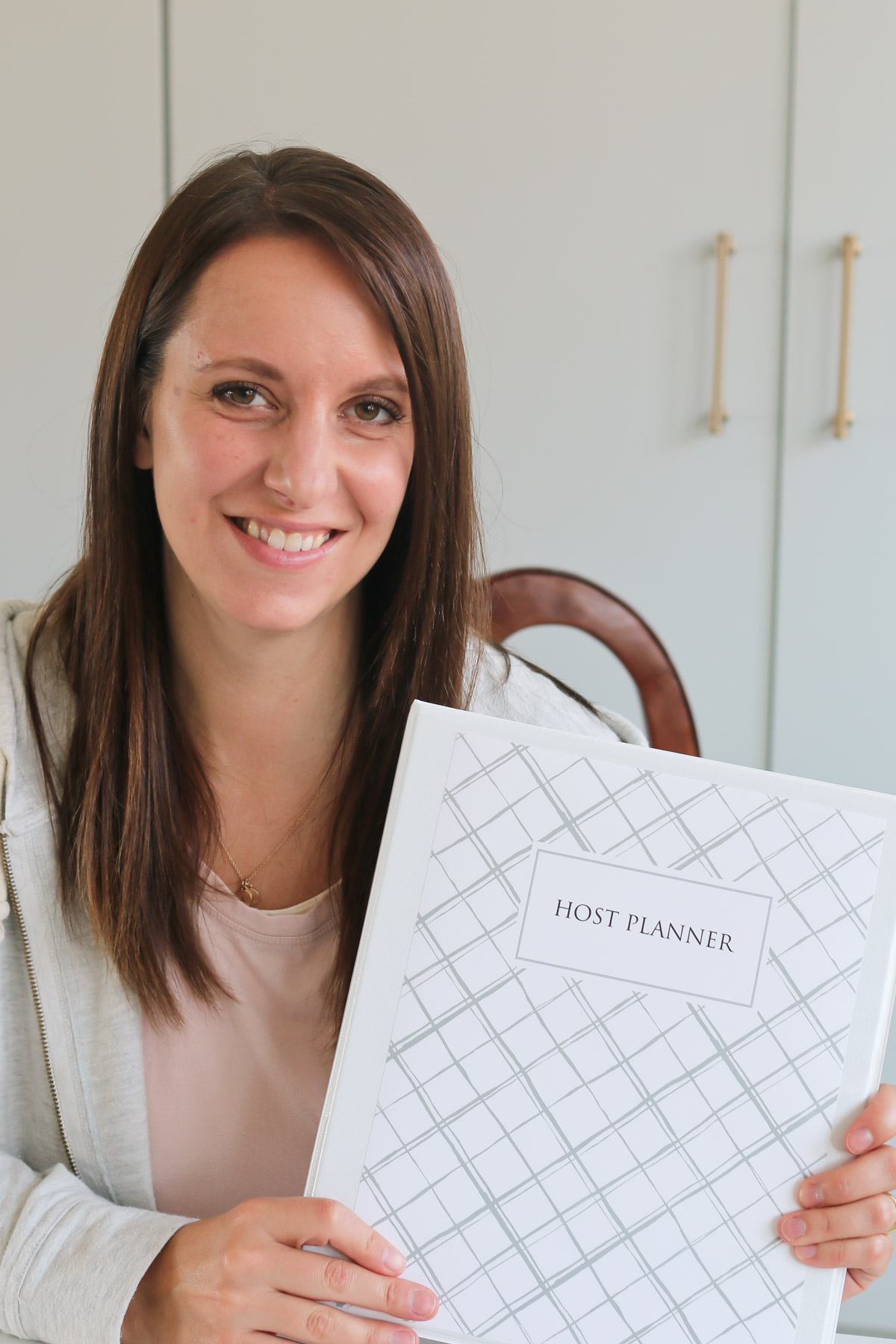 Cami holding a printed version of the Host Planner in a binder