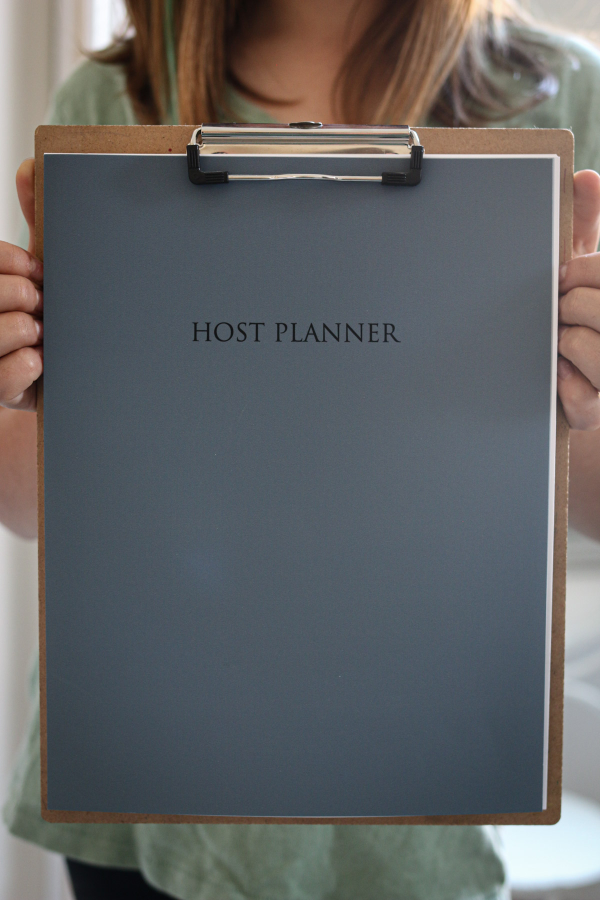 girl holding up a printed copy of the Host Planner attached to a clipboard