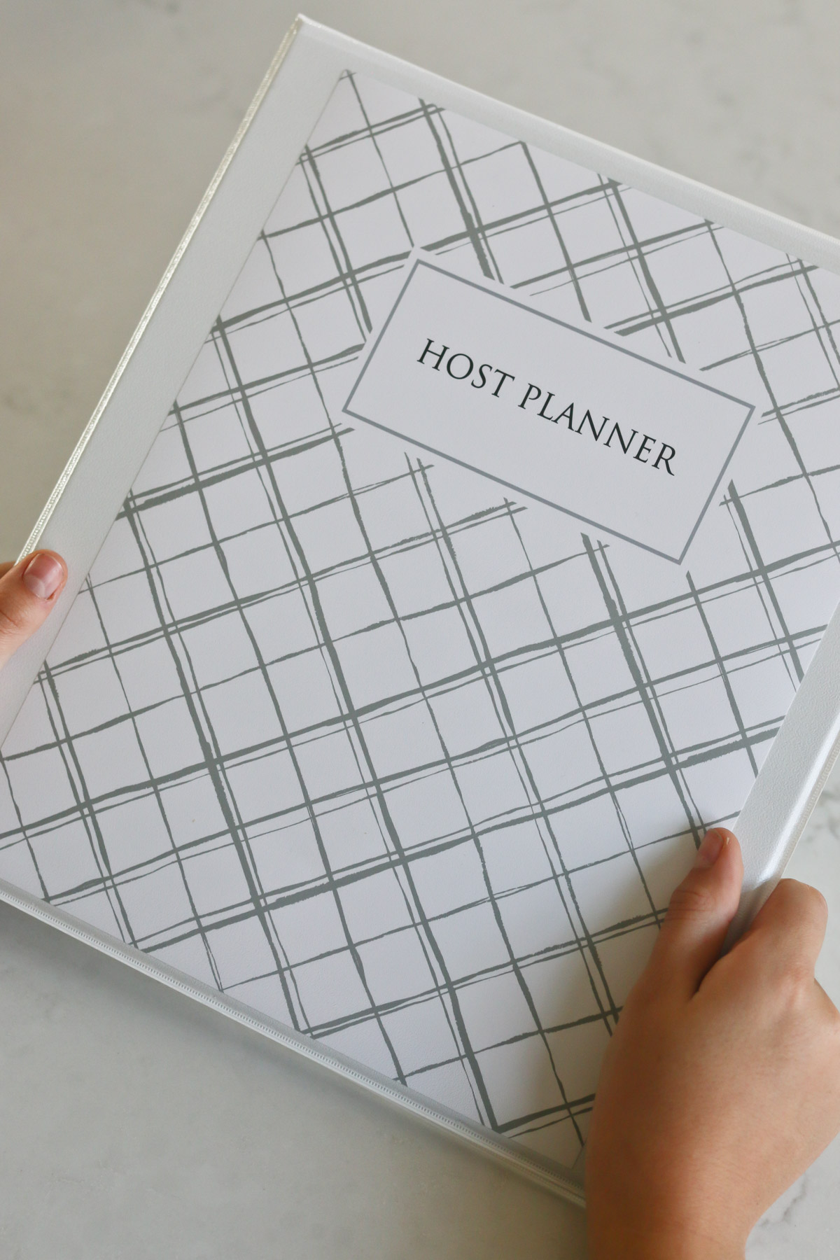 hands holding a copy of the Host Planner in a binder