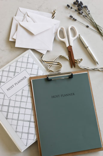 The Host Planner binder placed next to scissors, ribbon, a pen, and envelopes