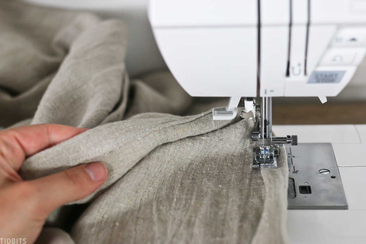 hand holding curtain under the needle of a sewing machine