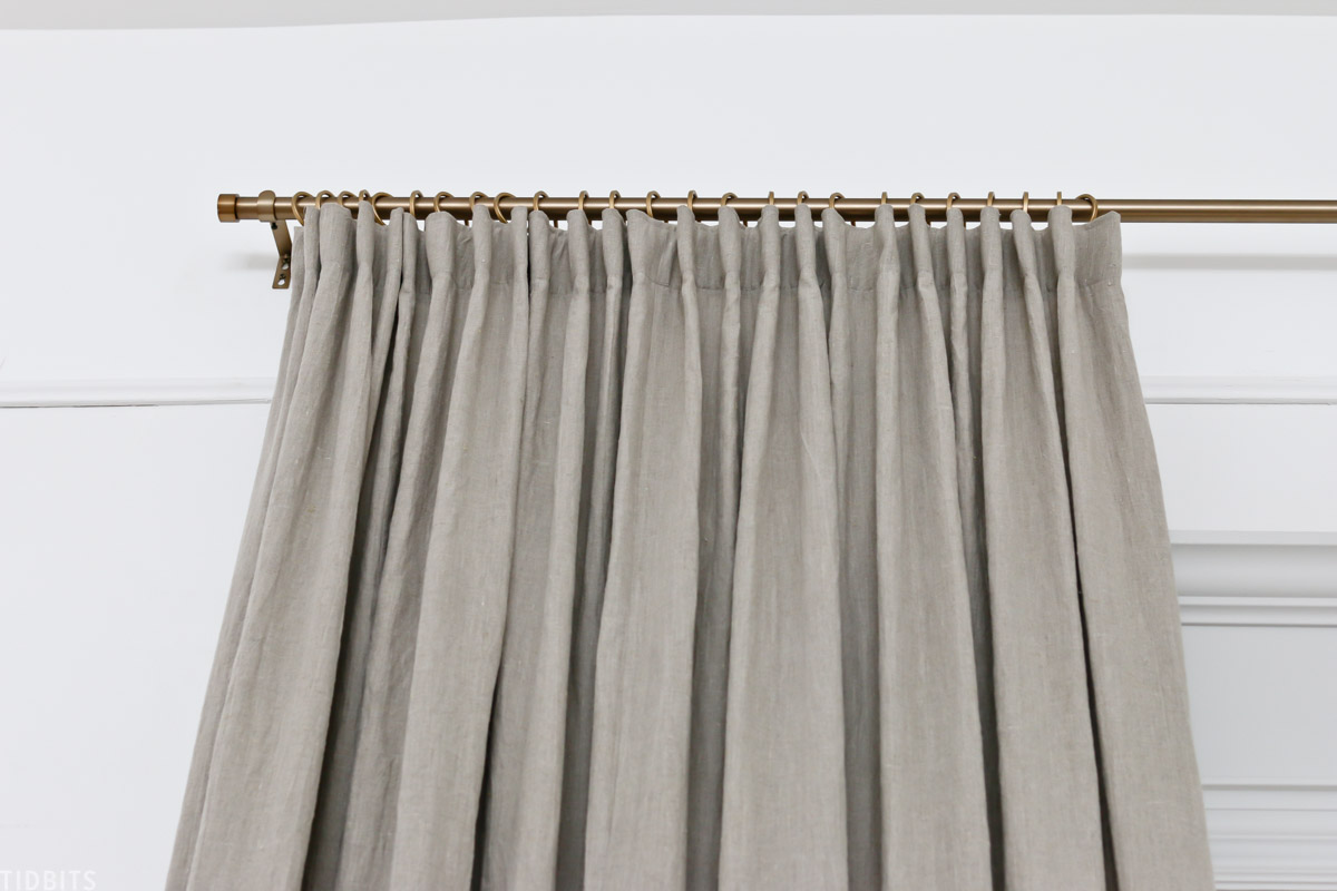 DIY pleated curtain hung on gold curtain rod with matching curtain rod rings