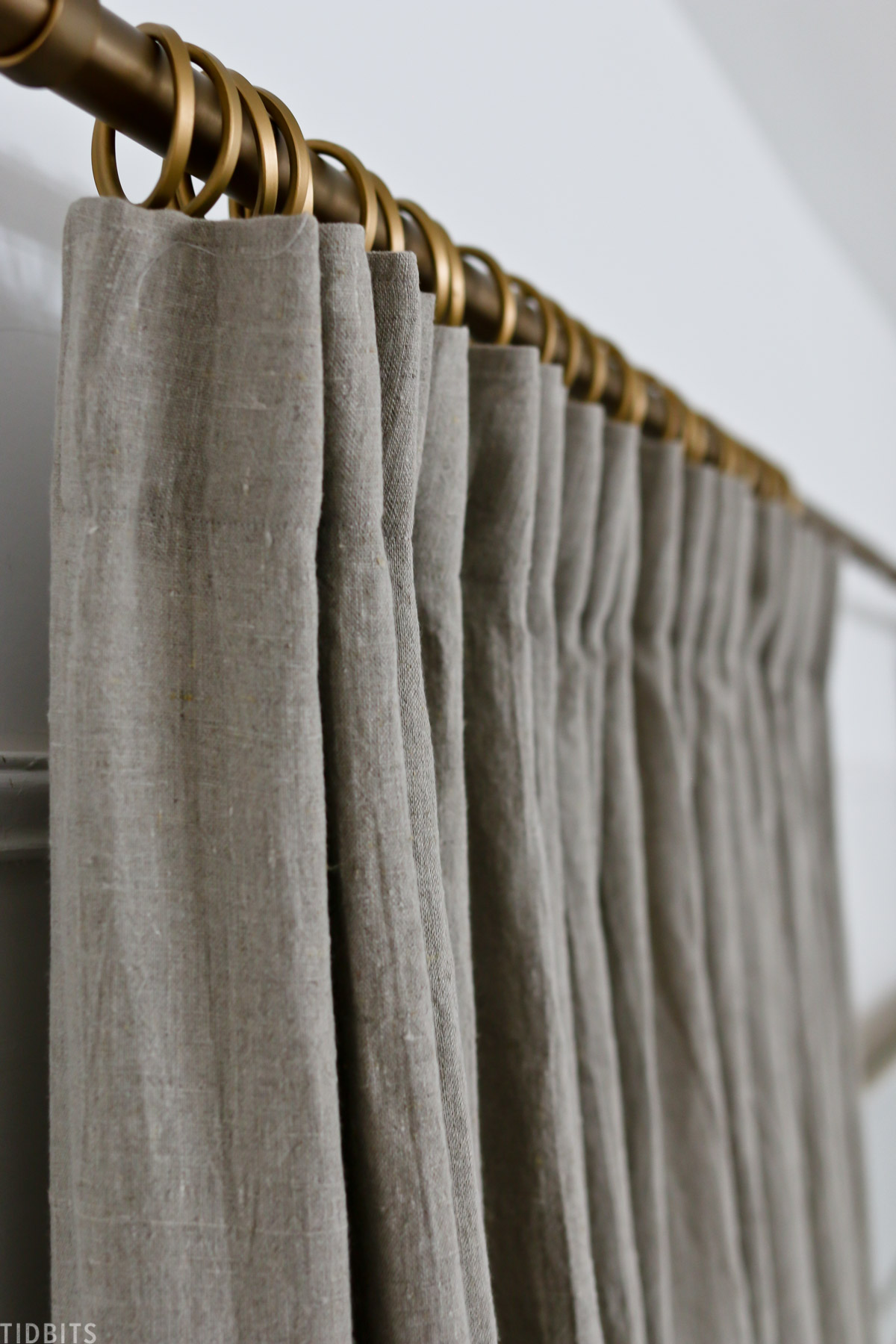 close up showing details on the DIY pleated curtains while it's hung on a golden curtain rod with golden curtain rod rings