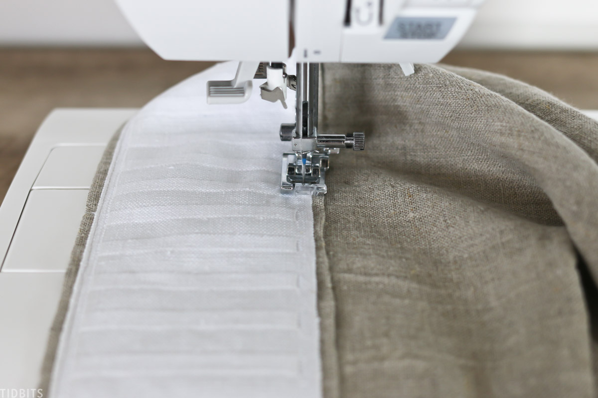 needle of sewing machine moving across top part of curtain