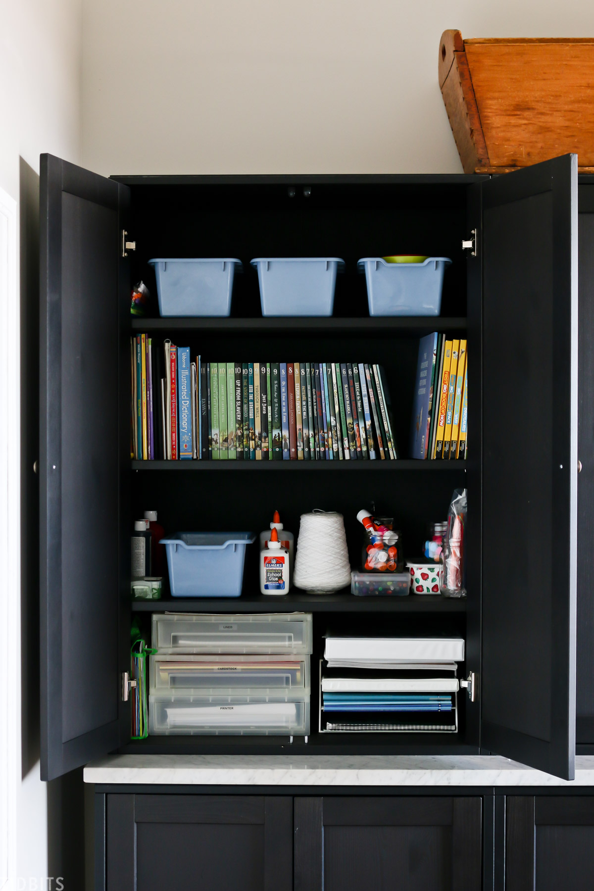 cupboard for homeschooling supplies like paper, binders, blue, and books