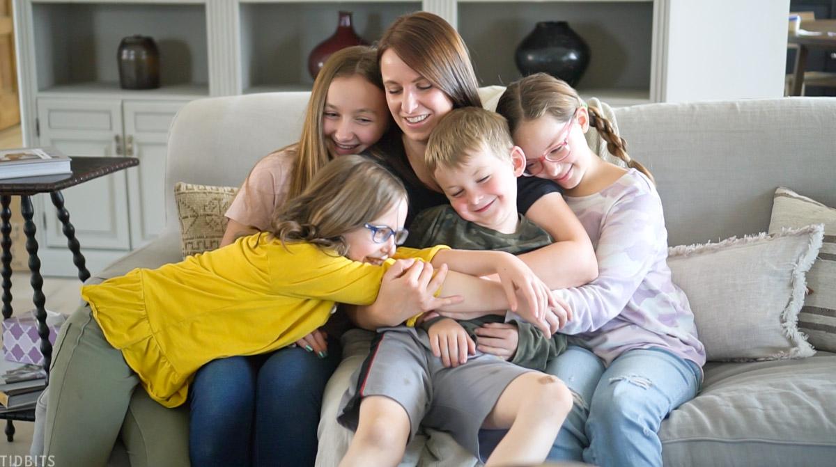 four kids hugging their mom
