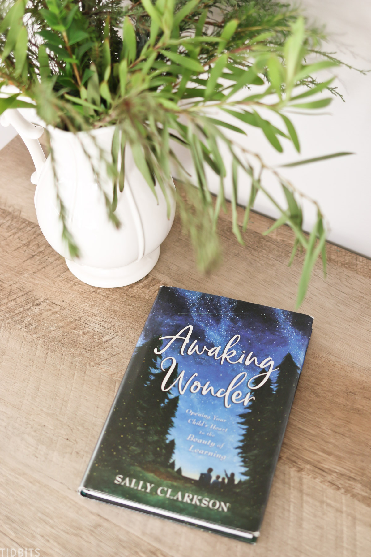 the book Awaking Wonder by Sally Clarkson on a side table next to a plant in a vase