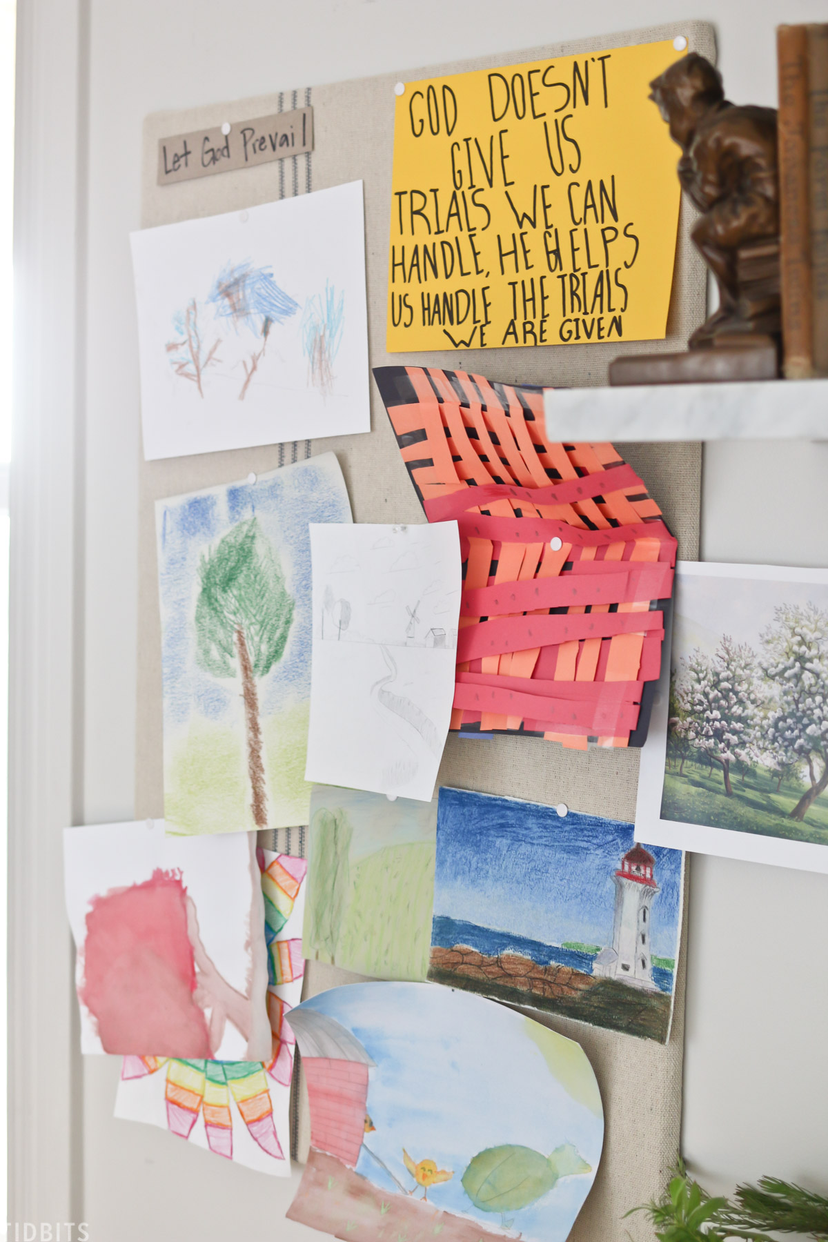 cork board hanging on a wall with various paintings and drawings made by kids