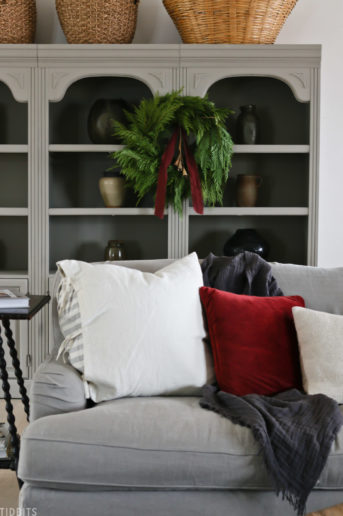 gray couch with decorative pillows with a Christmas wreath and red ribbon hanging above it