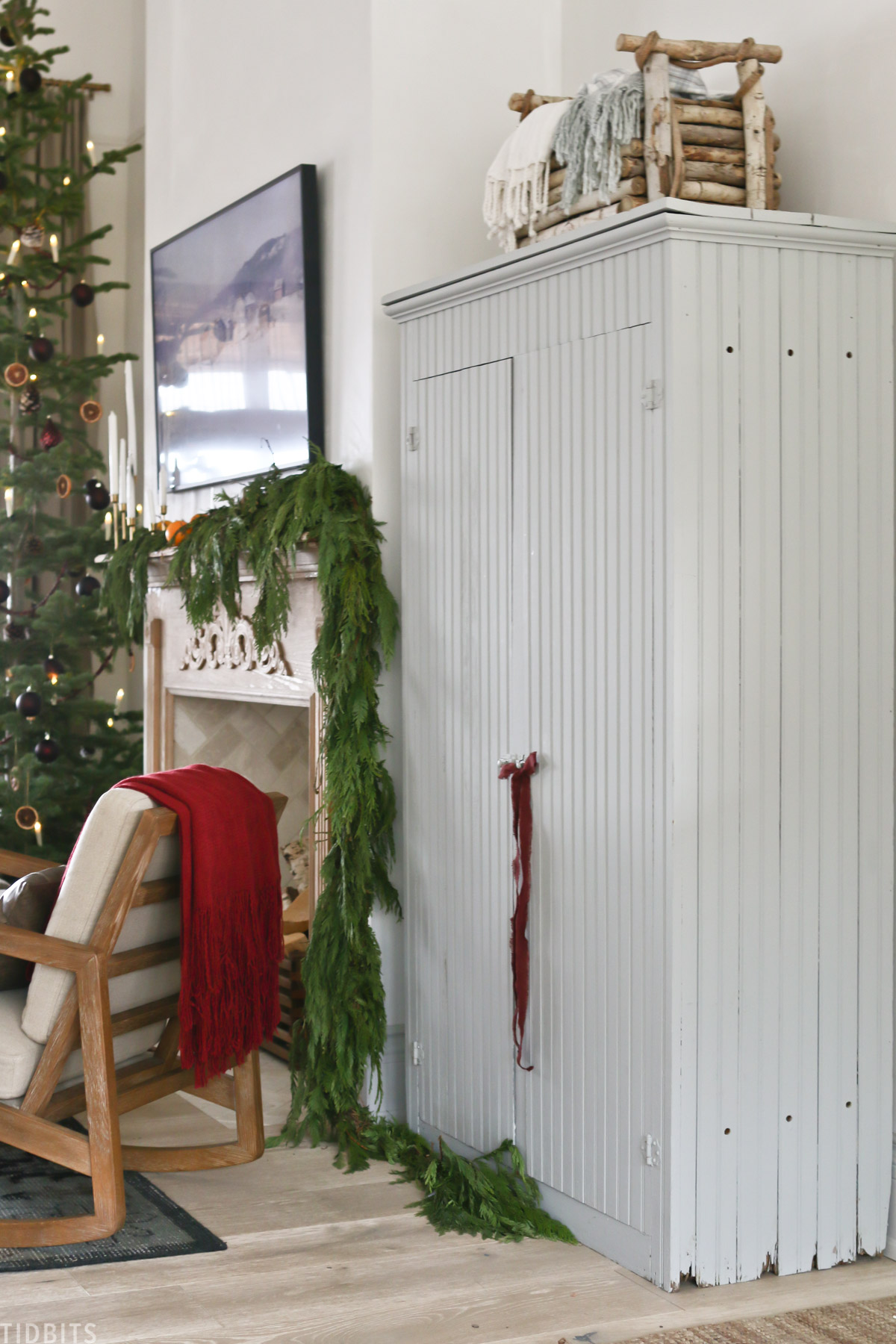 living room with ribbon tied to cabinet door handle and chair with red blanket with Christmas tree in background