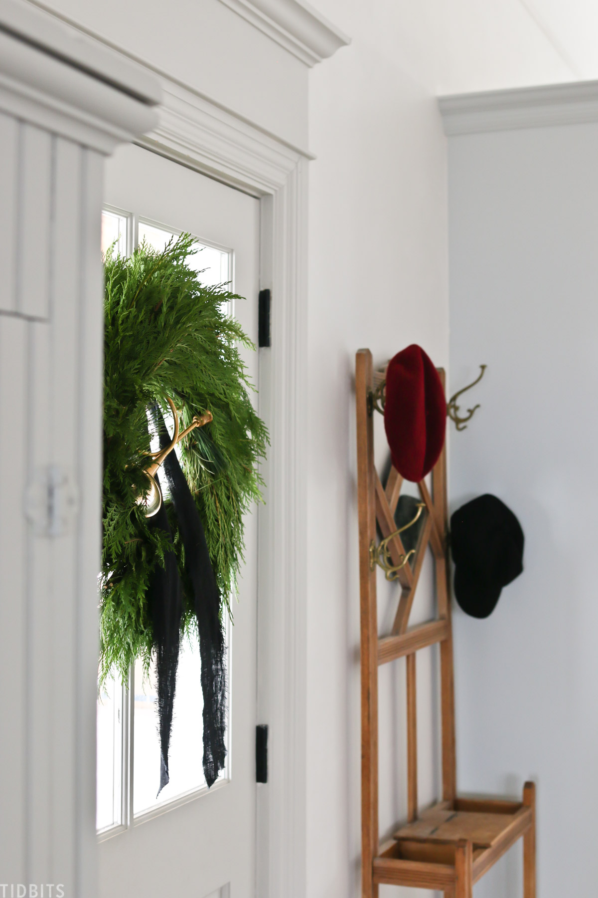 Christmas wreath hanging on front door with a coat wrack next to it