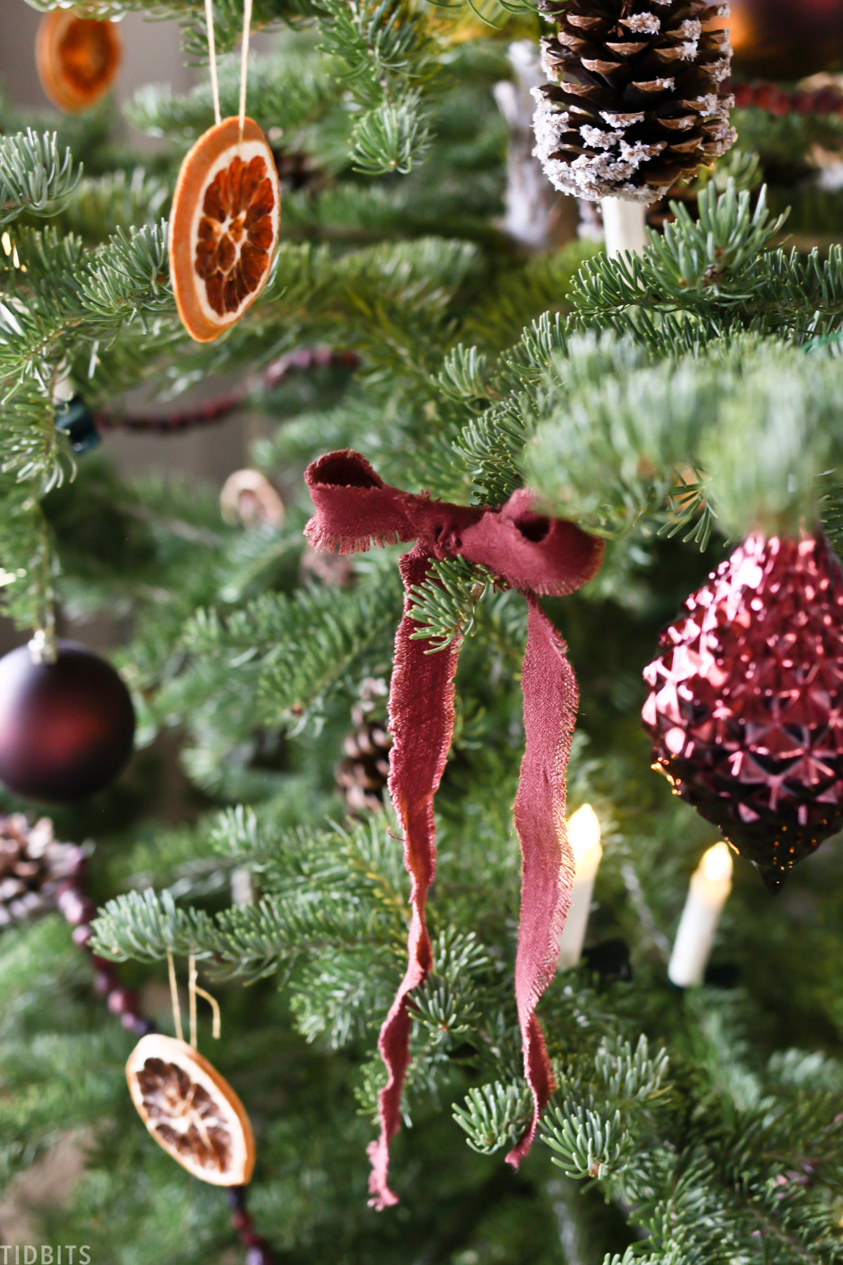 Christmas ornaments, candles and sliced oranges on a Christmas tree with a red linen ribbon