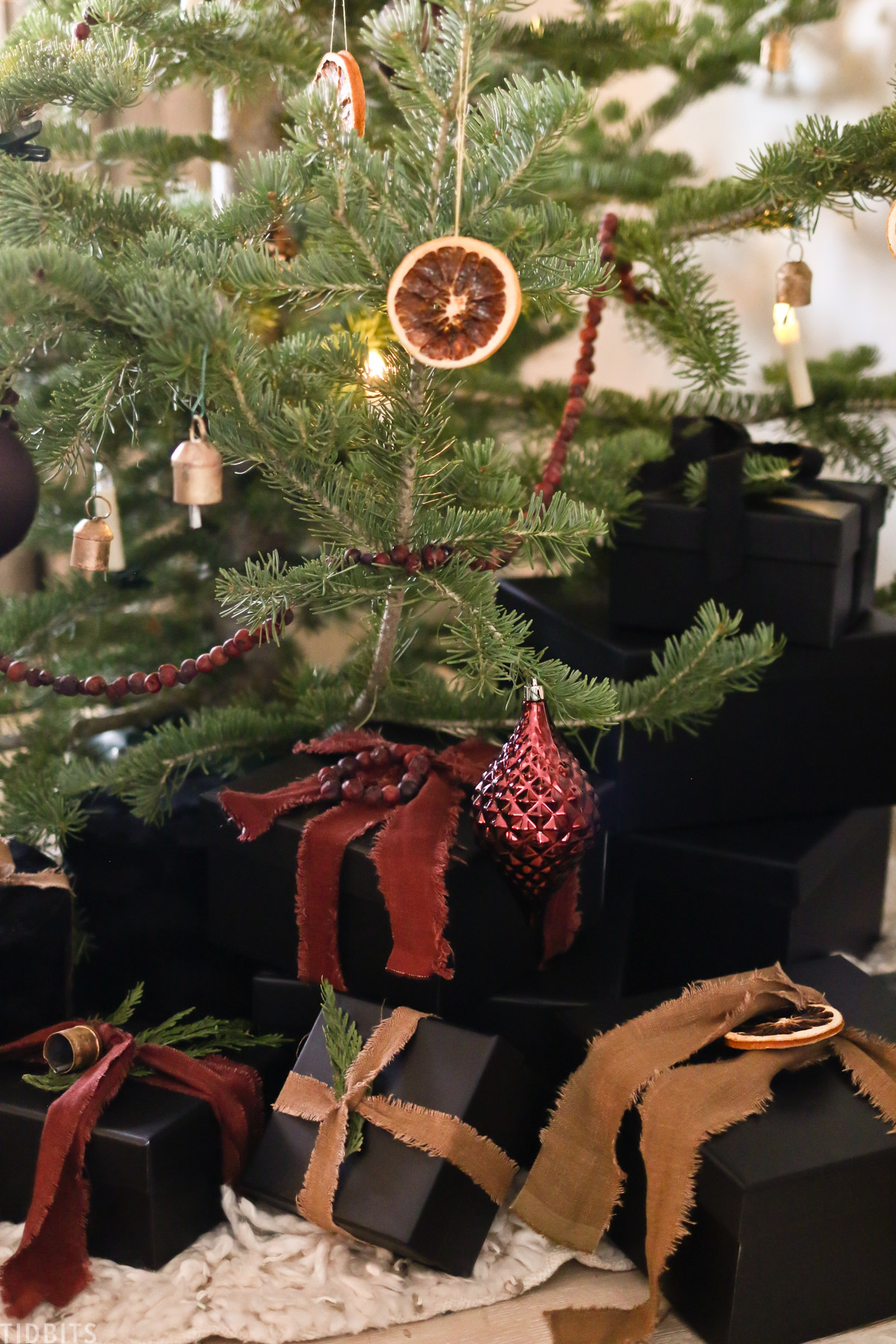 Christmas ornaments, candles and sliced oranges on a Christmas tree with a linen ribbon wrapped around presents under the tree