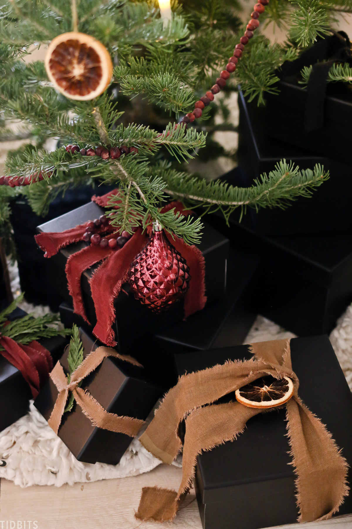 Christmas presents under a Christmas tree with orange and red linen ribbons