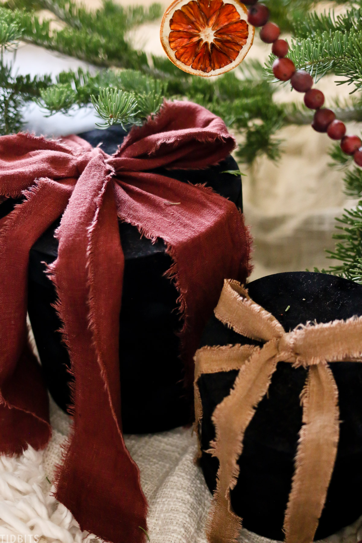 two Christmas presents under a Christmas tree with orange and red linen ribbons