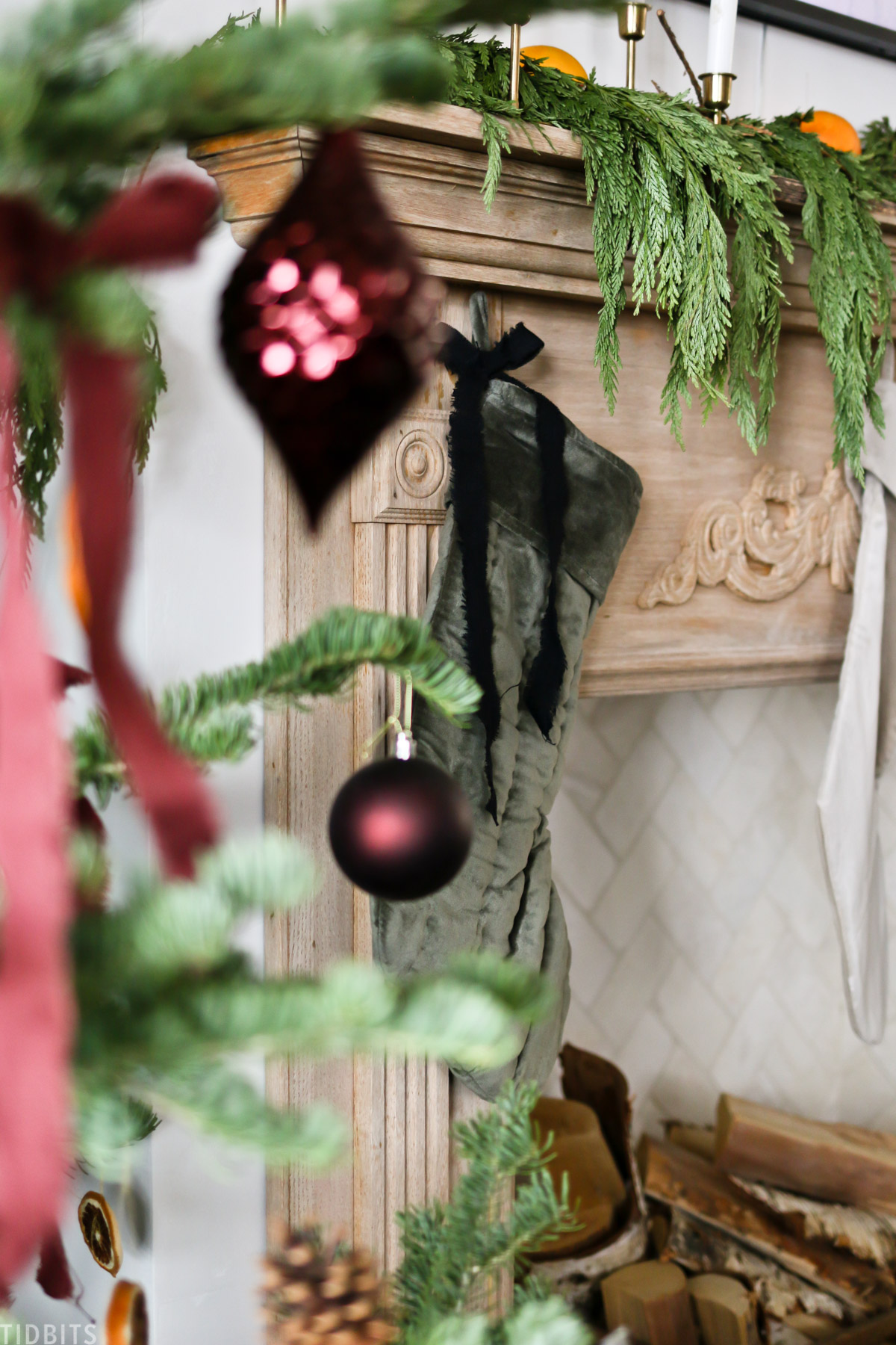 Christmas ornaments hanging from a Christmas tree with a mantel in the background decorated with Christmas decor