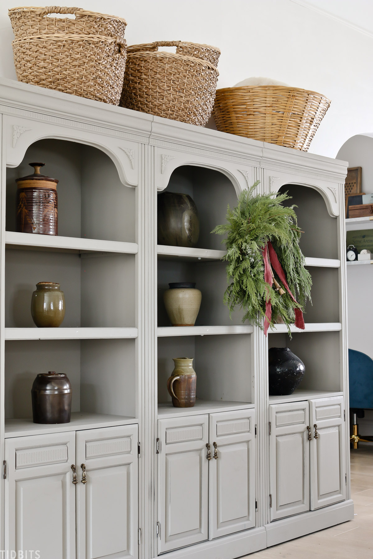 refurbished bookshelves with baskets and vases and wreath hanging from center bookshelf