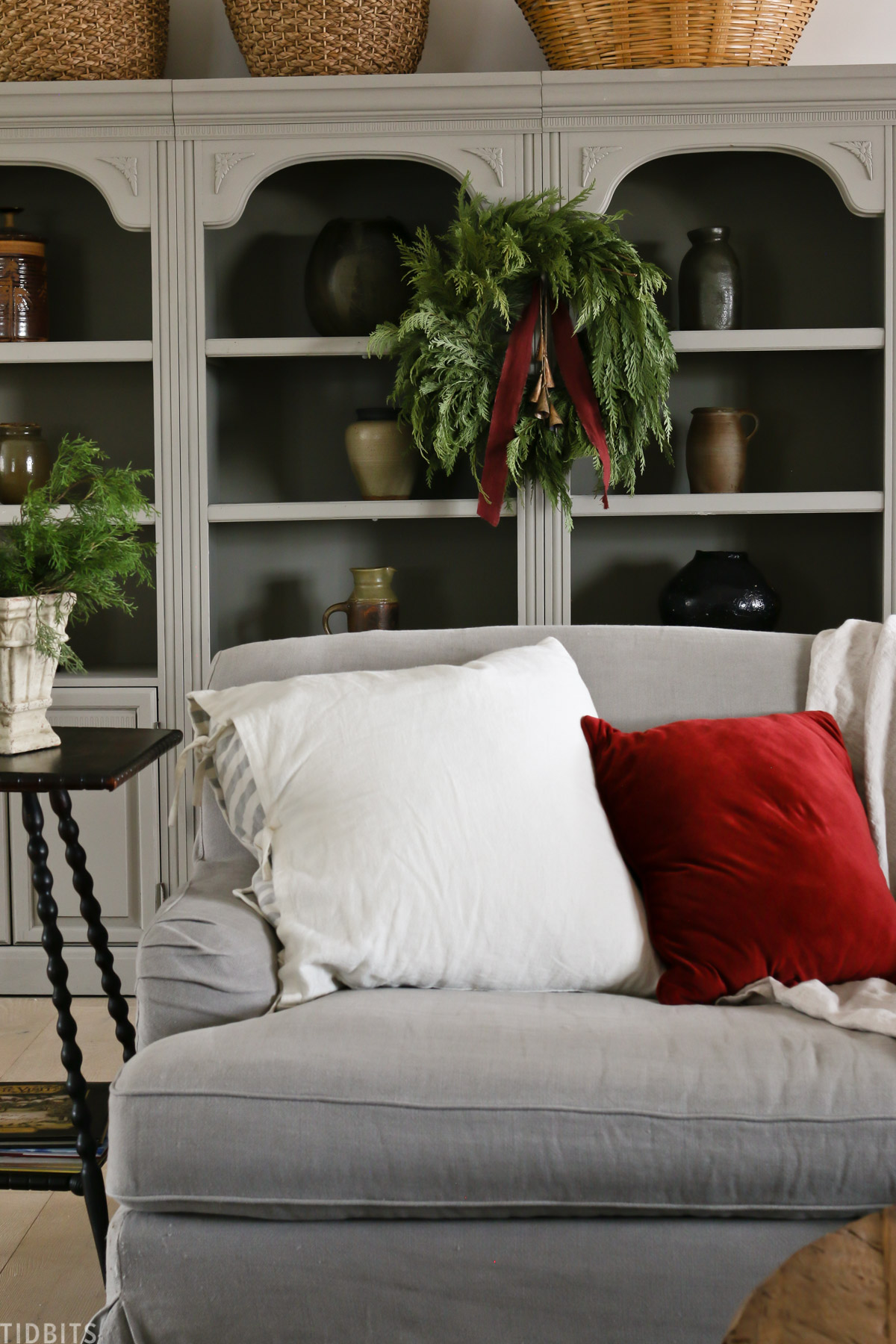 couch in front of refurbished bookshelves with baskets and vases and wreath hanging from center bookshelf