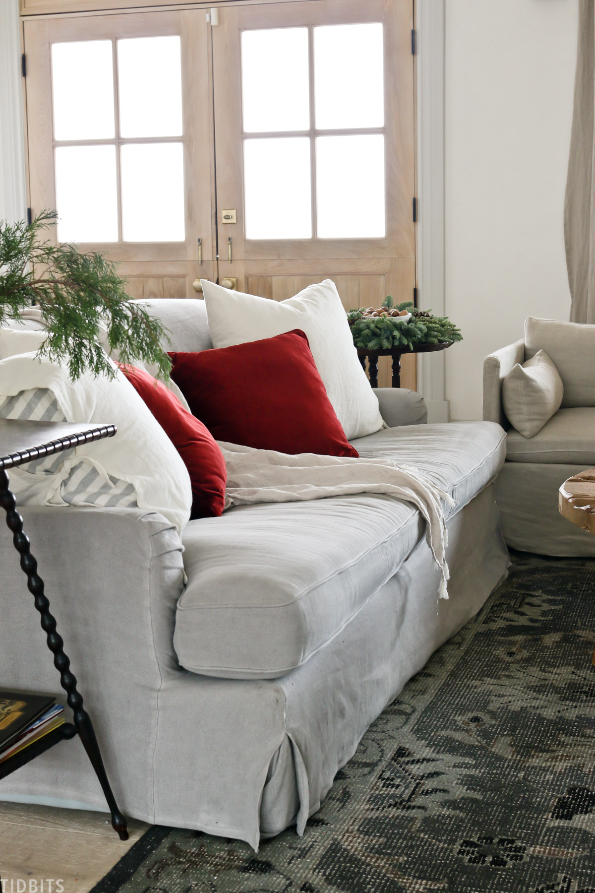 couch with red and white decorative pillows and throw blanket