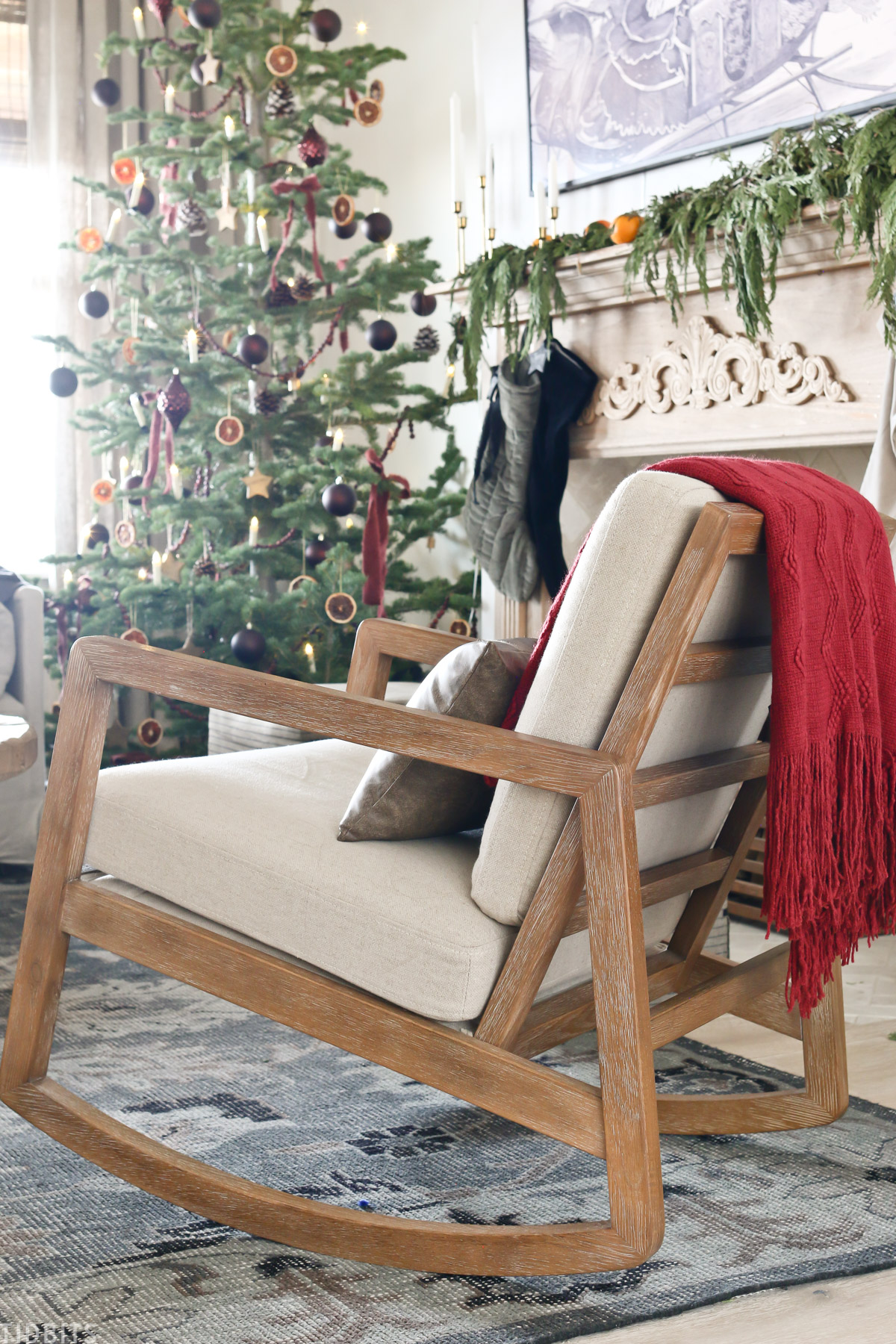 rocking chair in living room with Christmas tree in background and Christmas decorations on the mantel
