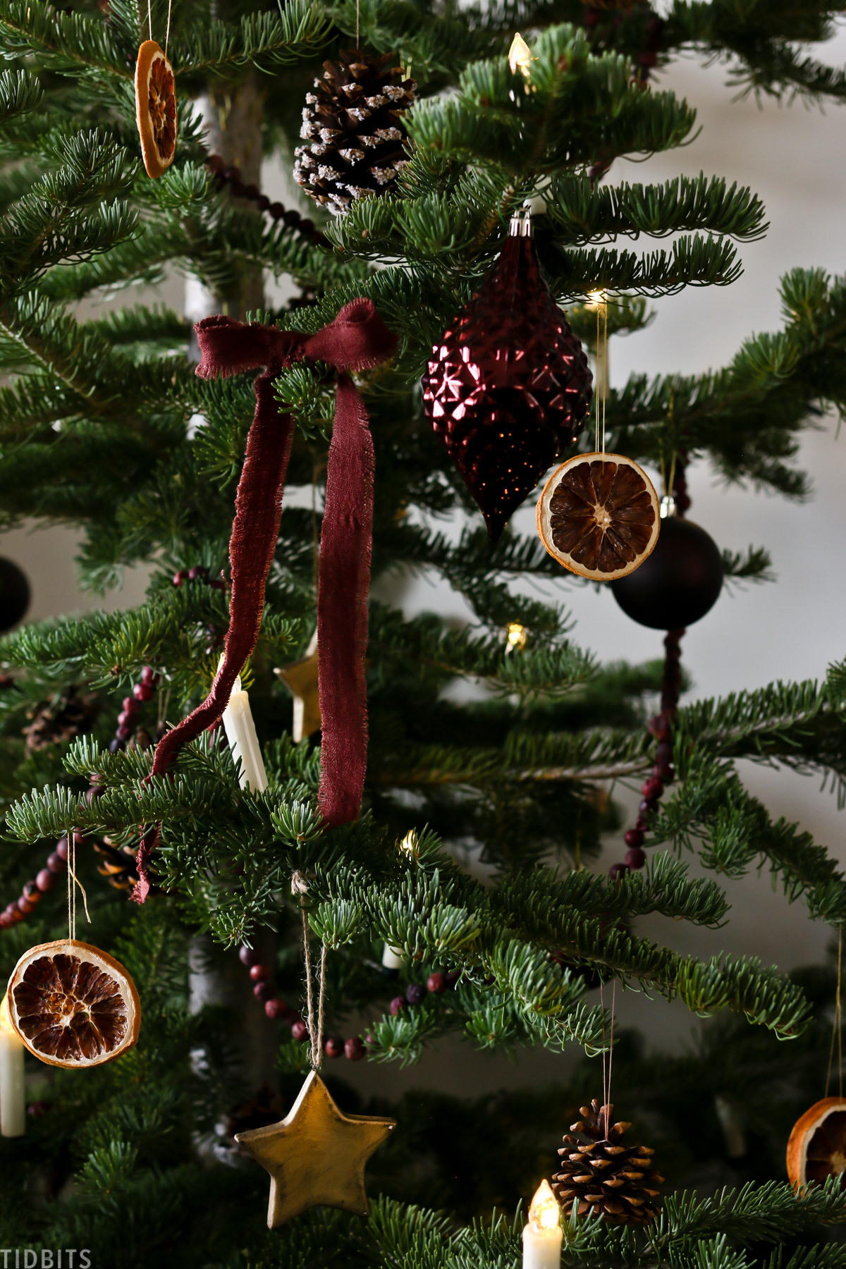 orange garlands, red ribbon and ornaments hanging from European Old World style Christmas tree