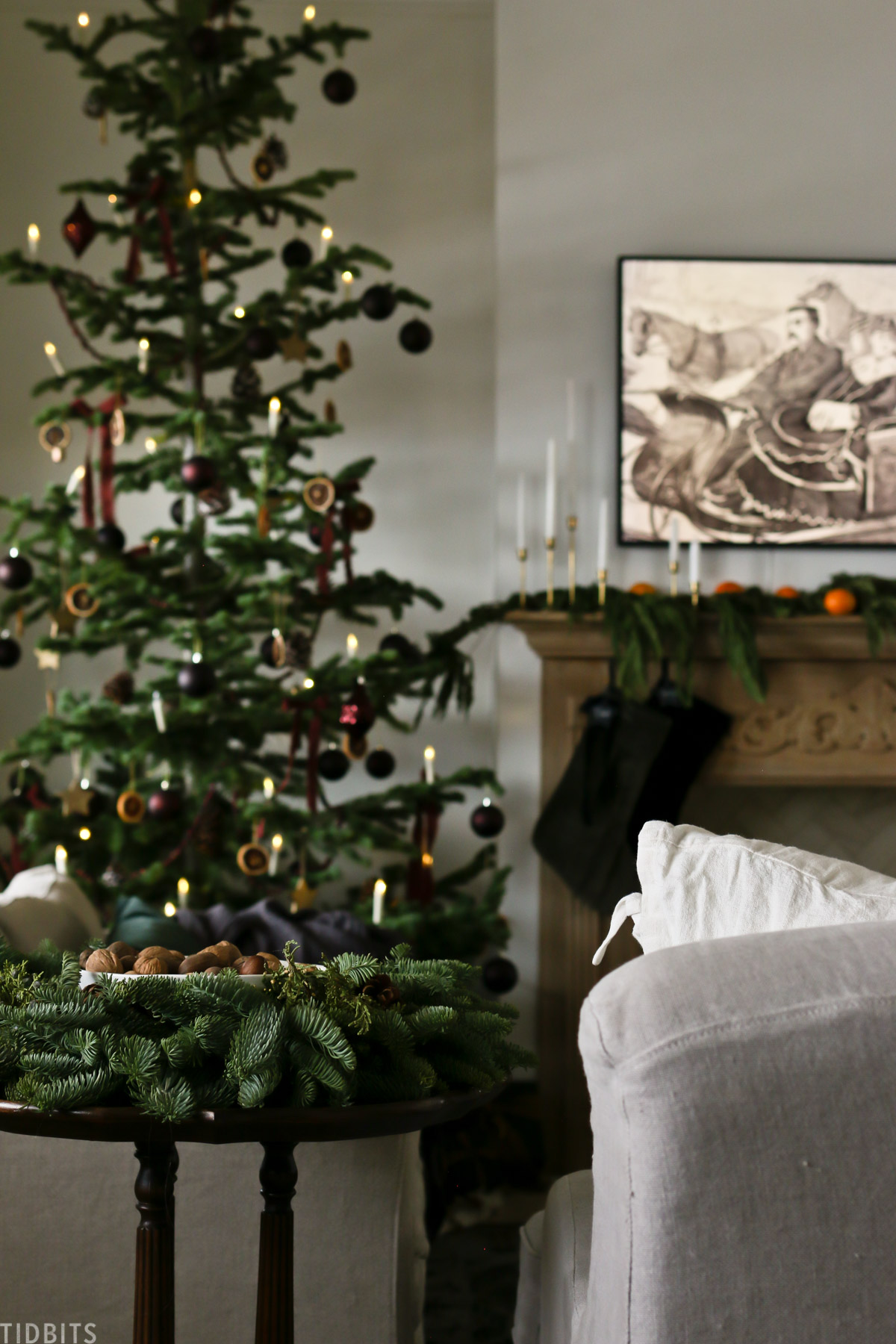 centerpiece that looks like a wreath is placed on side table next to couch with Christmas tree in background